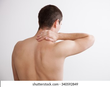 Young man touching his neck, white background