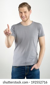 Young man touching an imaginary button on light background