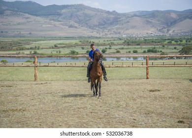 A young man touring the wild Mustang in a corral. In the steppes of Buryatia.