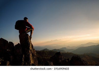 Young man tourist with backpack relaxing on top rock and enjoying sunset