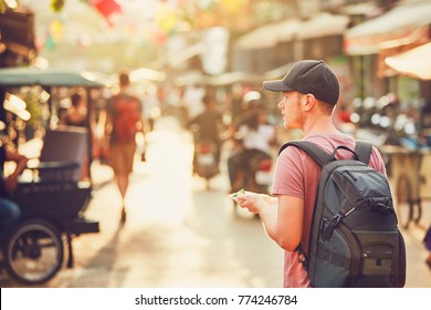 Young man (tourist)  with backpack walking to the night market buying tasty sweet food. Busy street full of restaurants, bars and shops. Siem Reap city at the sunset, Cambodia
