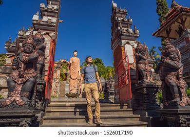 Young man tourist in budhist temple Brahma Vihara Arama Banjar Bali, Indonesia