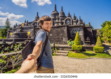 Young man tourist in budhist temple Brahma Vihara Arama Banjar Bali, Indonesia Follow me concept