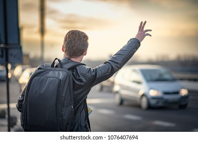 Young man tourist in a foreign city trying to hail a cab, holding a map to navigate himself