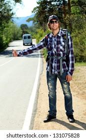 Young man tourist hitchhiking along a road.