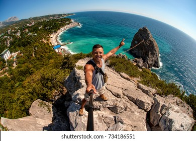 young man tourist make selfie, high on the mountain, on sea beach Crimea background, very joyfull and happiness