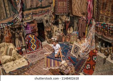 young man tourist at an old traditional Turkish carpet shop in cave house Cappadocia, Turkey Kapadokya
