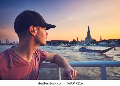 Young man (tourist) on the boat watching the traditional boats against temple Wat Arun. Bangkok at the sunset, Thailand.