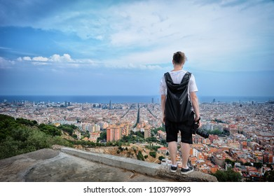 Young man tourist is standing on a edge roof and looking at the city. Barcelona. Spain