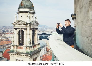 Young man (tourist) taking pictures with smart phone on Budapest, Hungary.