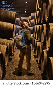 Young man tourist  walk in old aged traditional wooden barrels with wine in a vault lined up in cool and dark cellar in Italy, Porto, Portugal, France