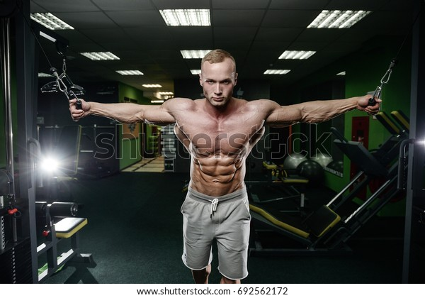 young man train in the gym healthcare lifestyle sexy caucasian man bodybuilder work out naked body torso