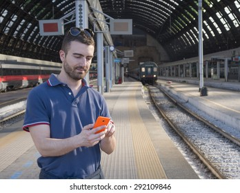 young man in train station using cellphone