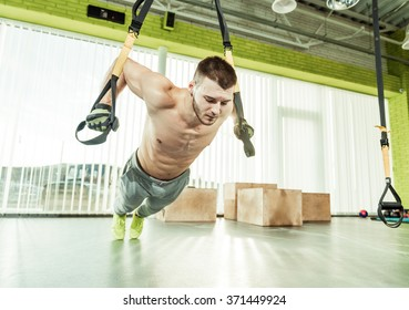 young man trainig on equipment in gym