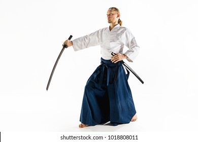 The young man are training in Aikido at studio with saber.Aikido master practices defense posture. Healthy lifestyle and sports concept. Man with beard in white kimono on white background. Karate man