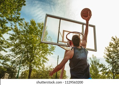 Young man is training basketball on the street court. He throw ball to the hoop. Rear view.