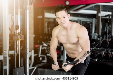 Young man training exercise push ups with fitness straps in the gym