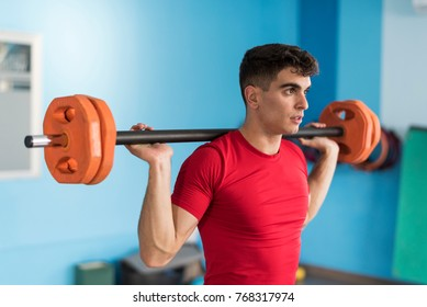 Young man training with fitness bar in gym with natural light