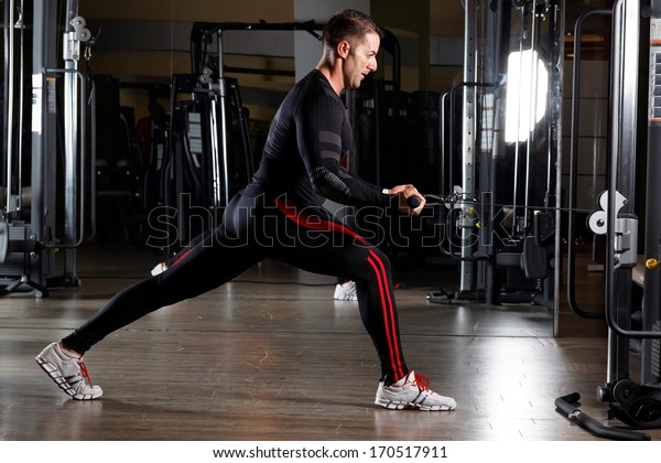 Young man training in the gym with heavy balls.Low light.