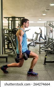 Young man training at gym legs and biceps exercises. Blurred man in background running in treadmill.Gymnasium indoor.