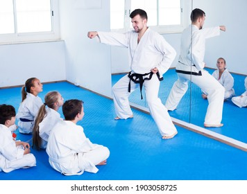 Young man training new karate moves with kids during class