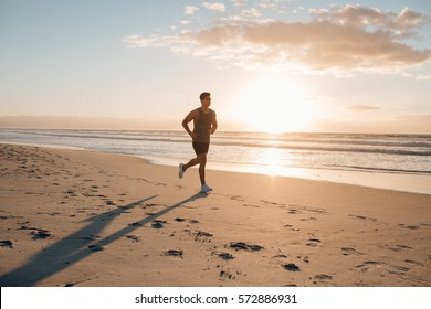 Young man training on the beach in morning. Young man on morning run outdoors.