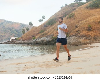 Young man training on the tropical beach in morning. Young man on morning run outdoors.