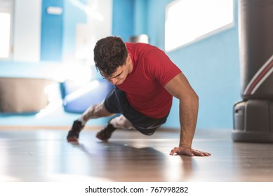 Young man trains push-ups in the gym on one hand