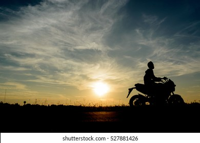 Young man and travel by motorcycle, Silhouette at sunset.