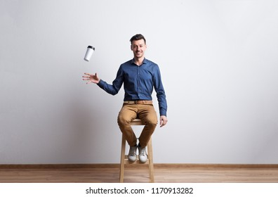 Young man with travel coffee mug in a studio sitting on a stool.