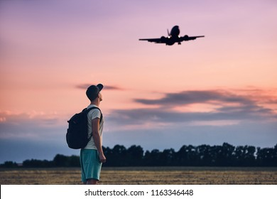 Young man (traveler) against moody sky with landing airplane. Prague, Czech Republic.