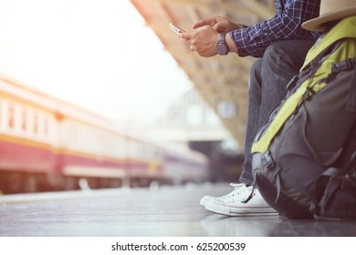 Young man traveler with backpack and hat use phone with waiting for train. Travel concept.