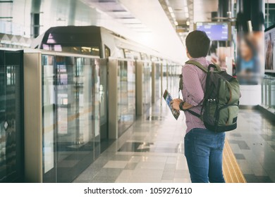 Young man traveler with backpack holding Kuala Lumpur location map in hands while looking MRT Train coming to platform in Kuala Lumpur, Malaysia.