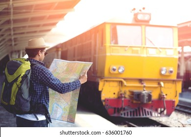 Young man traveler with  backpack prepare travel looking the map with waiting for train. Travel concept.