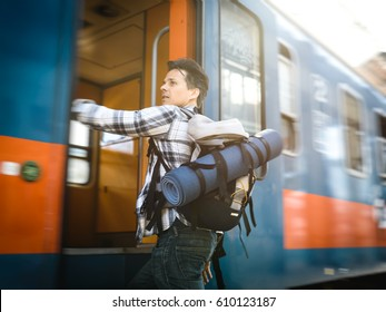 A young man traveler catching the train at the last moment