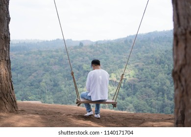 Young man traveler enjoying on wooden swing on the mountain