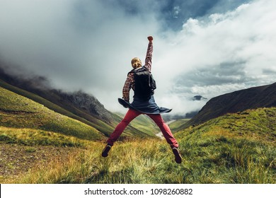 Young man traveler jumps on a background of mountain and enjoys view of summer mountains. Concept of achieving motivation. Rear View