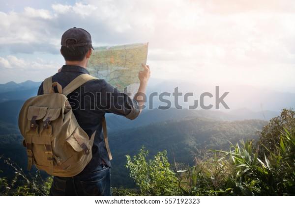 Young Man Traveller mit Karte Rucksack entspannend draußen mit felsigen Bergen auf dem Hintergrund Sommerurlaub und Lifestyle Wanderkonzept.