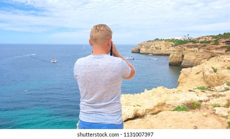 young man traveler and photographer standing and looking at the landscape