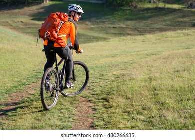 Young man traveler riding on bicycle with red backpack