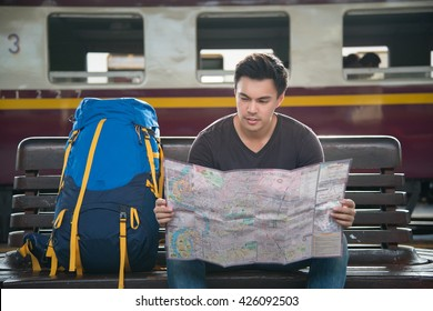 A young man traveler sitting with map choose where to travel and bag waiting for train at train station