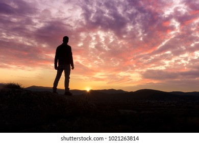 A young man traveler standing  enjoy with beautiful sunset on top of the mountain.