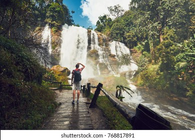 Young man (traveler) standing near Wachirathan waterfall in tropical rainforest. Chiang Mai Province, Thailand