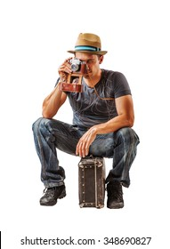 young man traveler takes a shot on vintage camera while sitting on a suitcase isolated on white background
