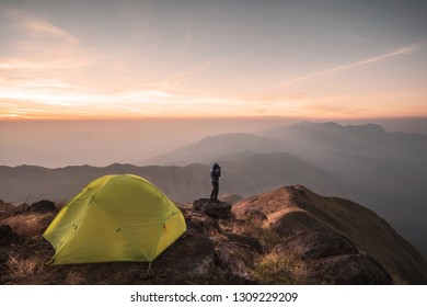 Young man traveler taking a photo and camping on mountain, Adventure travel lifestyle concept