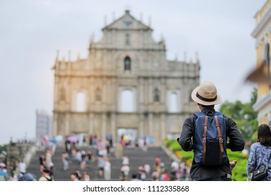 Young man traveling backpacker with hat, Asian hipster traveler looking to Ruins of St. Paul's, Historic Centre of Macau, a UNESCO World Heritage Site. landmark and popular for tourist attractions