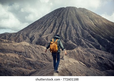 young man traveling and hiking standing on rock mountain vulcano
