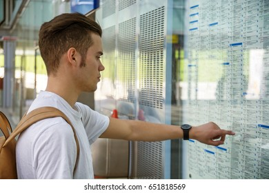 Young man traveling, pointing finger on train timetable in railway station
