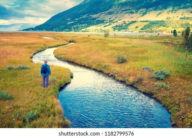 Young man travels along a mountain river. Beautiful nature of Norway
