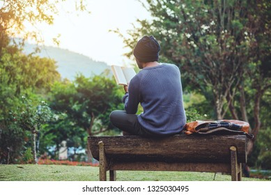 The young man travels nature on the mountain, is sitting and relaxing, reading a book in the flower garden.